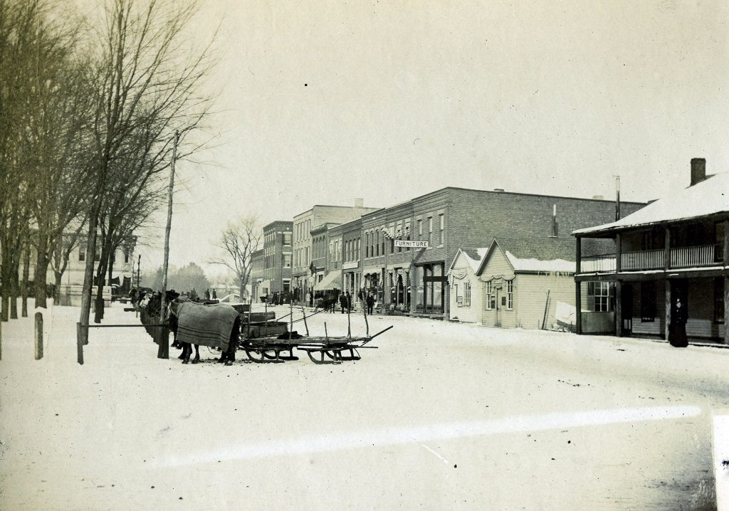 Horse-drawn sleds are parked along a snowy street in Lancaster, WI